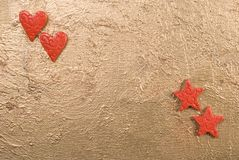 Hearts and Stars. Red hearts and stars on a golden surface Stock Images