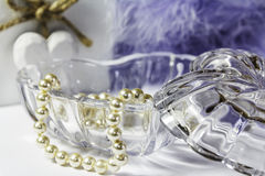 Hearts. A Still Life of a heart shape glass trinket jar with pearls.  Also a wooden heart and feather boa in the background Royalty Free Stock Images