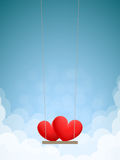 Hearts on swing. Couple of red hearts on swing in the daytime sky with clouds Royalty Free Stock Photos