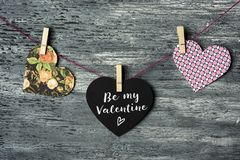 Hearts and text be my valentine. Some hearts hung with clothespins in a clothes line and a black heart-shaped signboard with the text be my valentine written in royalty free stock image