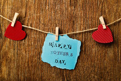 Hearts and text happy mothers day. The text happy mothers day written in a piece of blue paper hanging in a rope with a wooden clothespin next to some red hearts Stock Photo