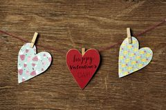 Hearts and text happy valentines day. Some hearts hung with clothespins in a clothes line and a red heart-shaped signboard with the text happy valentines day stock photos