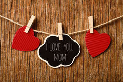 Hearts and text I love you mom. The text I love you mom written in a chalkboard in the shape of a thought bubble hanging in a rope with a wooden clothespin next Stock Photo