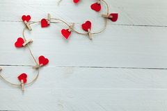 Hearts with tweezers. Red hearts subjects with tweezers on white wooden background royalty free stock photo