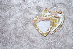 Hearts. Two wooden hearts decorated with bows and yellow glittering frames over rustic cement background, top view with copy space Stock Photos