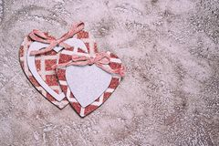 Hearts. Two wooden hearts decorated with bows and glittering frames over rustic cement background, top view with copy space Royalty Free Stock Photos