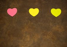Hearts of various colors on brown background for St. Valentine`s Stock Image