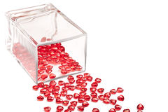 Hearts and Vase. Some red plastic hearts scattered out of a clear glass vase onto a white background Royalty Free Stock Images