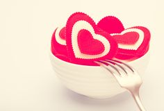 Hearts in a white bowl with a fork. Toned in warm colors Royalty Free Stock Images
