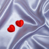 Hearts on white silk Stock Images