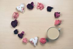 Hearts, wilted flowers and cup of coffee on pastel wooden background. Hearts, wilted flowers and cup of coffee Royalty Free Stock Photography