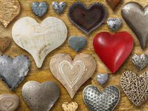 Hearts on wood background. Photos of many heart-shaped things made of stone, metal and wood on wood background Royalty Free Stock Photography