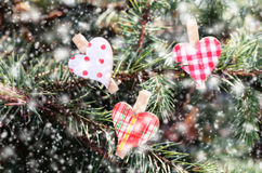 Hearts on xmas tree and falling snow Stock Photo