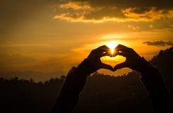Heartsets da mão das silhuetas e a laranja do céu Foto de Stock Royalty Free