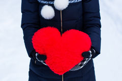 Heartshape pillow in woman's hands at winter day. Stock Image