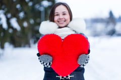 Heartshape pillow in woman's hands at winter day. Royalty Free Stock Photo