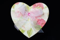 Heartshaped box. Heart shaped box with a pink ribbon and a flower design royalty free stock photography