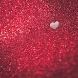 Red glittery background with a heartshaped cutout. A heartshaped cutout hole in a glittery background conceptual valentines day background royalty free stock photography