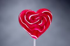 Heartshaped lollipop candy on grey background. Lollipop shaped as a heart for valentines day on grey background Royalty Free Stock Photography