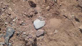 Heartshaped rock on a sandy road. A beautifull heartshaped lightgrey rock on a sandy road in Gran-Canaria royalty free stock image