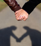 Heartshaped shadow. Shadow of couple heartshaped. Two hands holding each other outdoor. Focus on hands, blurred way stock photo