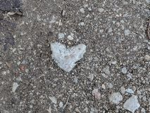 Heartshaped stone on the footpath. Heartshaped stone which was lying embeded in earth on the footpath royalty free stock photo