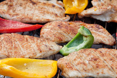 Hearty barbecue. Fresh turkey steaks with pepper on a grill Stock Images