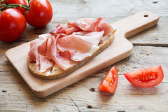 Hearty bread with ham  bacon  on a wooden board Stock Photo