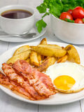 Hearty breakfast with bacon, fried egg and potato. Hearty breakfast with bacon, fried egg, potato and cup of coffee Royalty Free Stock Photos