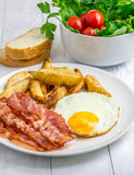 Hearty breakfast with bacon, fried egg, potato and vegetables. On the wooden table Stock Photography