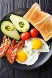 Hearty breakfast: fried eggs with bacon, avocado, toast and toma royalty free stock photos