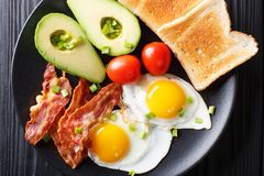 Hearty breakfast: fried eggs with bacon, avocado, toast and toma royalty free stock image