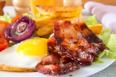 Hearty breakfast. Fried eggs with bacon fried potatoes with slices of tomatoes on lettuce leaves stock photo