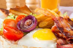 Hearty breakfast. Fried eggs with bacon fried potatoes with slices of tomatoes on lettuce leaves royalty free stock photo