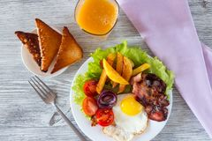 Hearty breakfast. Fried eggs with bacon fried potatoes with slices of tomatoes on lettuce leaves stock images