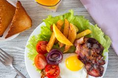 Hearty breakfast. Fried eggs with bacon fried potatoes with slices of tomatoes on lettuce leaves stock photos