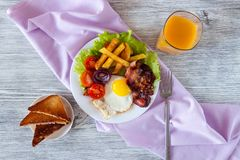 Hearty breakfast. Fried eggs with bacon fried potatoes with slices of tomatoes on lettuce leaves royalty free stock photos