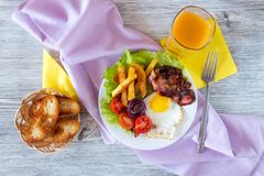 Hearty breakfast. Fried eggs with bacon fried potatoes with slices of tomatoes on lettuce leaves royalty free stock image