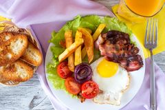 Hearty breakfast. Fried eggs with bacon fried potatoes with slices of tomatoes on lettuce leaves royalty free stock photography