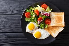 Hearty breakfast: fried eggs with fresh vegetable salad and toast close-up. horizontal top view. Hearty breakfast: fried eggs with fresh vegetable salad and stock image