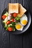 hearty breakfast: fried eggs with fresh vegetable salad and toast close-up. vertical top view stock image