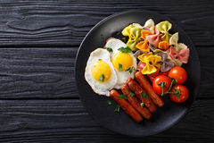 Hearty breakfast: fried eggs, sausages, farfalle pasta and tomat Stock Photography