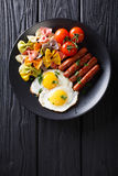 Hearty breakfast: fried eggs, sausages, farfalle pasta and tomat Stock Photos