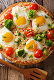 Hearty breakfast of pizza with eggs, broccoli, tomatoes closeup Royalty Free Stock Photos
