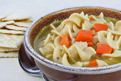 Hearty Chicken Noodle Soup with Carrots. A crock of hearty chicken noodle soup, close-up. Crackers to the side stock photo