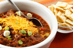 Hearty chili with cheese and scallions. A hearty bowl of chili topped with shredded cheese and scallions makes a tasty lunch or dinner stock images