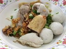 Hearty eating meal noodle with  fish ball, fishcake slices and boiled pork for light breakfast or lunch focus on foreground with b Royalty Free Stock Photo