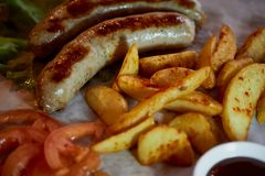 Hearty, fatty dish to the table. Beer.German national cuisine. Fried sausages with fried potatoes and sauce. Hearty, fatty dish to the table. Beer. German Royalty Free Stock Images