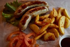 Hearty, fatty dish to the table. Beer.German national cuisine. Fried sausages with fried potatoes and sauce. Hearty, fatty dish to the table. Beer. German Royalty Free Stock Photos
