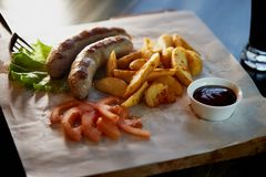 Hearty, fatty dish to the table. Beer.German national cuisine. Fried sausages with fried potatoes and sauce. Hearty, fatty dish to the table. Beer. German Stock Photos